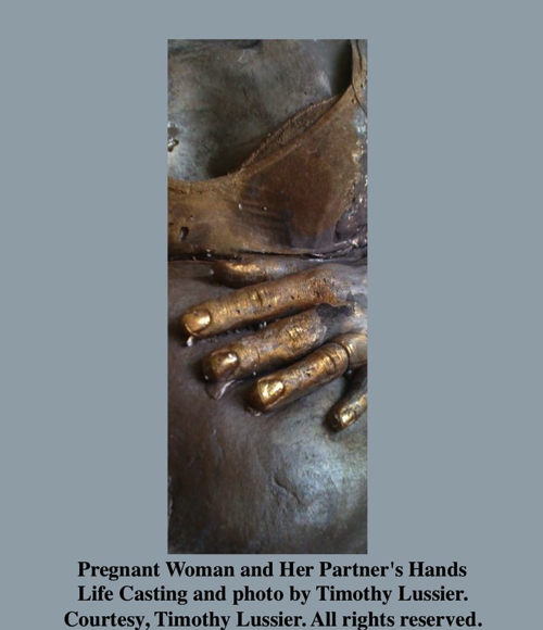 Photograph of pregnant woman with gold painted hand of partner on her abdomen
